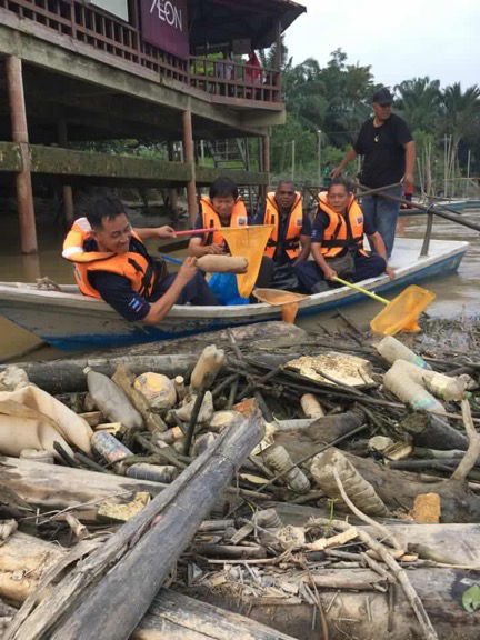 Malaysia-clean-up-team-fishing-plastic-bottles-from-the-water.jpg